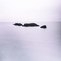 Three small, rocky islands projecting from the ocean, with a light purple haze