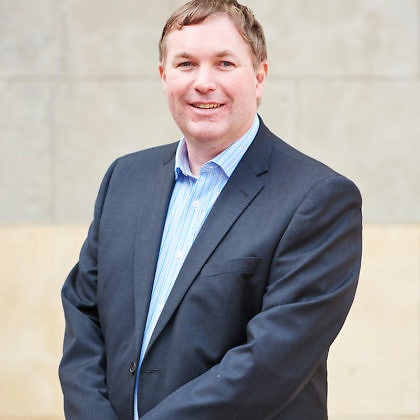 Portrait of Dr. Scott Hollier standing against a limestone wall, outside. Scott wears a blue suit and holds his arms in front of him.
