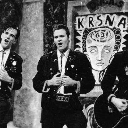 DAAS performing in their iconic style. There are three men wearing black leather jackets, singing the band member to the right is holding an acoustic guitar, this is occurring behind a backdrop of some abstract artwork.