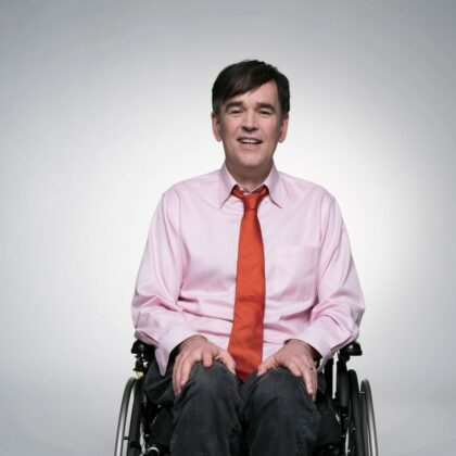 Tim, wearing a salmon shirt with an orange tie on his wheelchair. Behind a white backdrop.