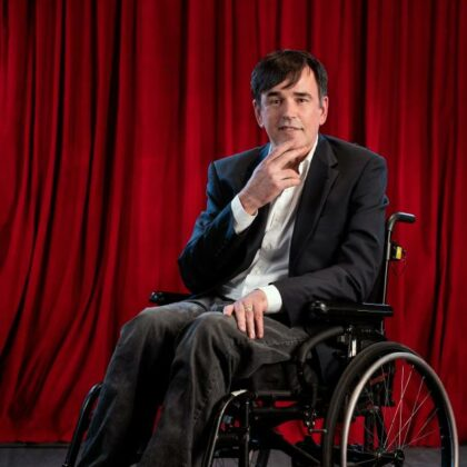 Tim, wearing a suit on his wheelchair. Behind a red curtain backdrop