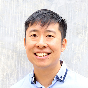 Stanley Lai smiling at the camera. He wears a light blue shirt with a two layered collar.