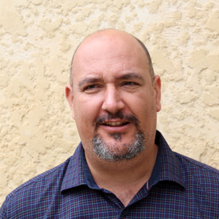Portrait of Stewart Luxton. Stewart wears a dark blue collared shirt with a light check pattern.